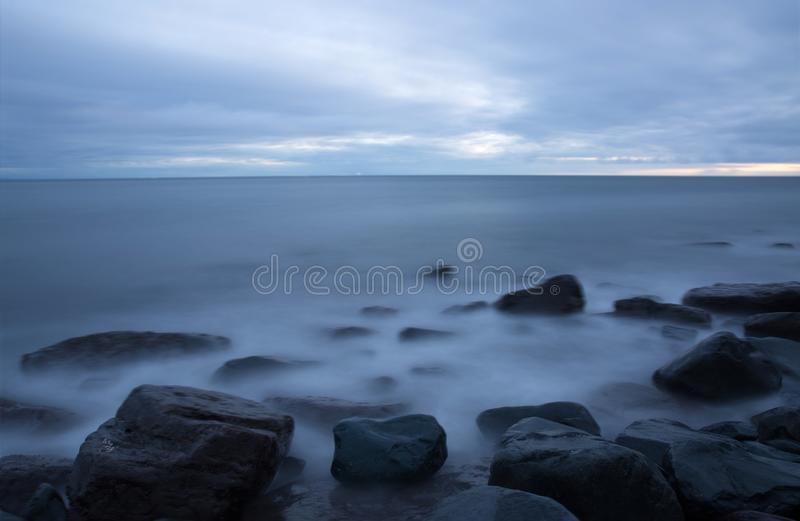 Ocean fale i wodny gnanie nad skalistym jetty zdjęcia stock