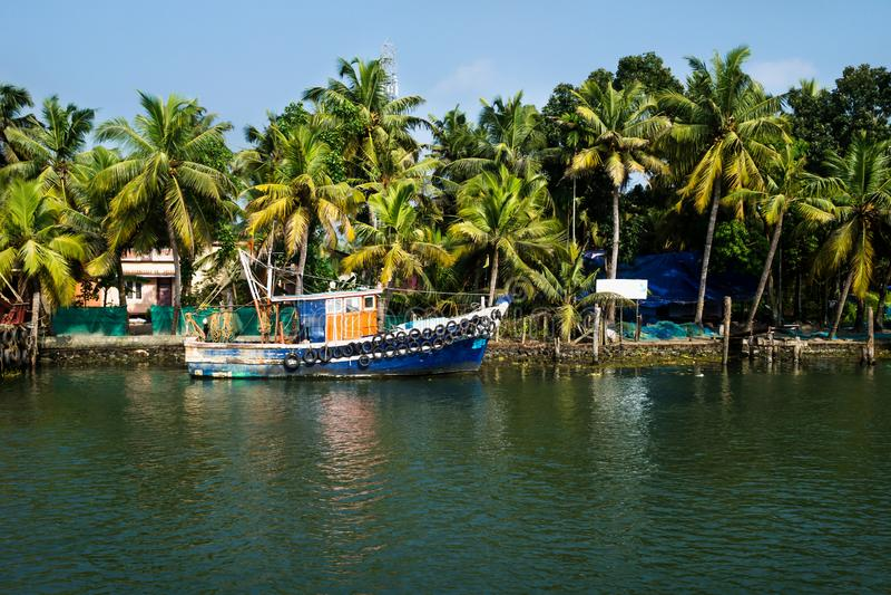 Ocean fishing boat along the canal Kerala backwaters shore with palm trees between Alappuzha and Kollam, India. Ocean fishing boat along the canal Kerala stock photo