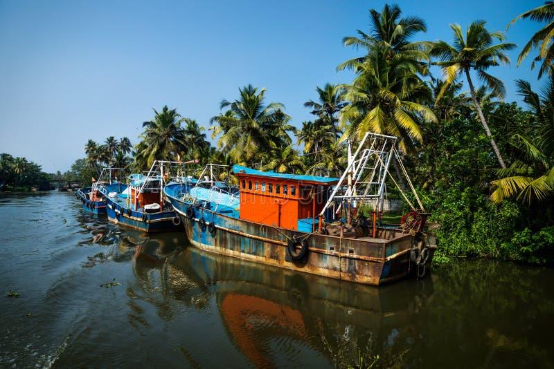 Ocean fishing boats along the canal Kerala backwaters shore with palm trees between Alappuzha and Kollam, India. Ocean fishing boats along the canal Kerala royalty free stock photo