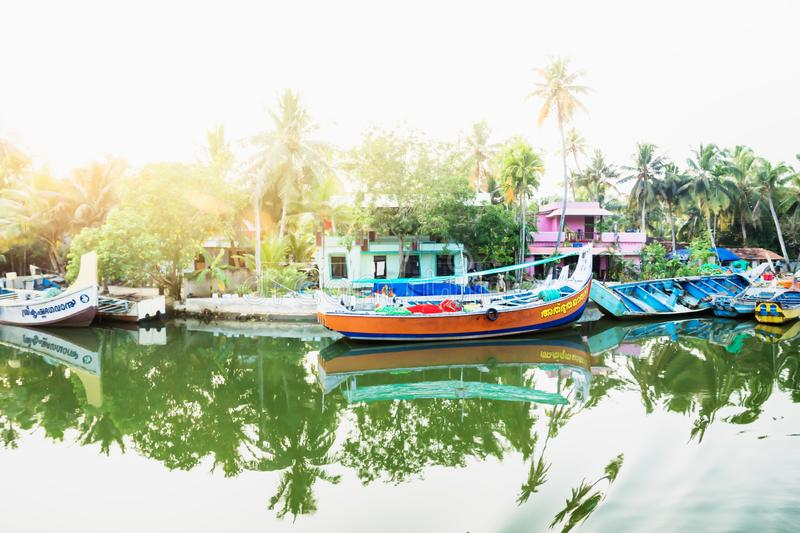 Ocean fishing boats with lens flare along the canal Kerala backwaters shore with palm trees between Alappuzha and Kollam, India. Ocean fishing boats with lens royalty free stock image