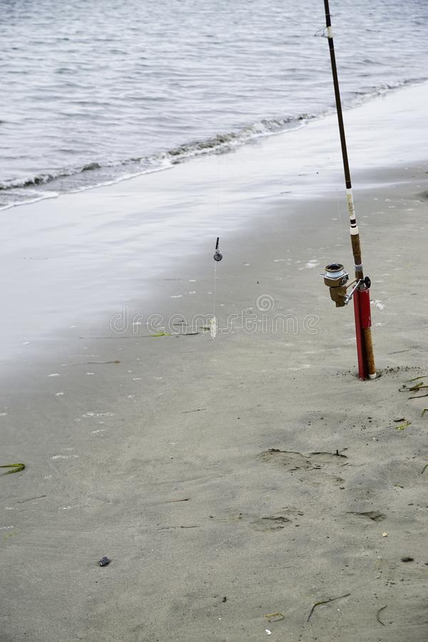 The Baited Fishing Pole. Ocean fishing pole baited and ready to cast, standing up in sand. Close-up stock image
