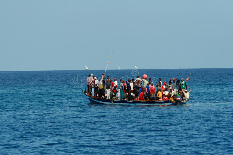 In ocean floats your boat with large group of Africans. stock image