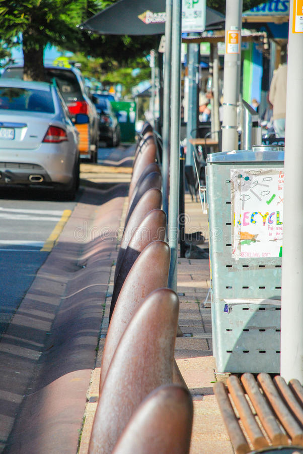Ocean Grove Terrace street, Victoria, Australia. Bollards in the shape of shark& x27;s fin, cars parked along the street, bench and recycling bin in the view. A royalty free stock photos