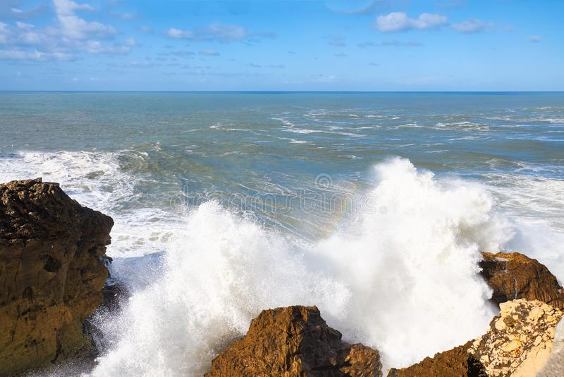 Ocean Huge waves crashing on the rocks of Nazare. stock photo