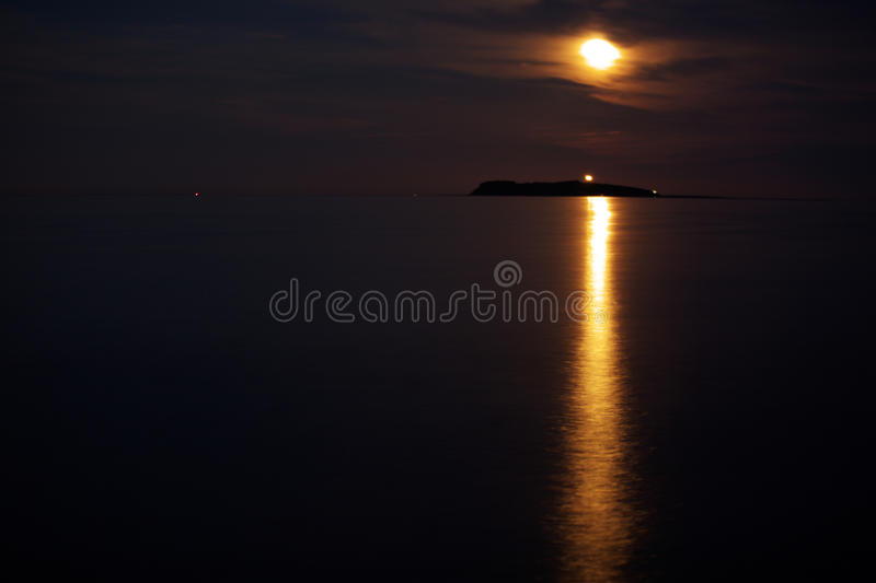 Ocean island lightened by beam of moonlight royalty free stock photos