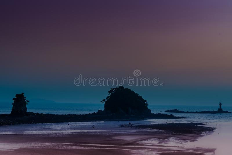 Ocean islets and lighthouse during. Ocean islets and lighthouse during low tide at sun set with beautiful blue and maroon sky in background stock photography