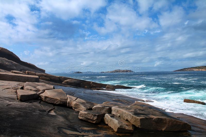 The ocean laps against a smooth rocky shoreline. The foamy sea laps against a smooth rocky shoreline in Esperance, Western Australia. There are some large rocks stock image