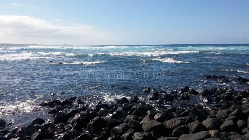 Ocean of light. The atlantic ocean shines on the volcanic black rocks of Lanzarote stock image