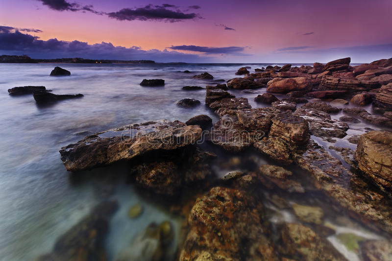 Ocean Manly Shelly Pink Set. Sydney famous manly beach area rocky formation at sunset vivid pink sky and blurred water long exposure stock images