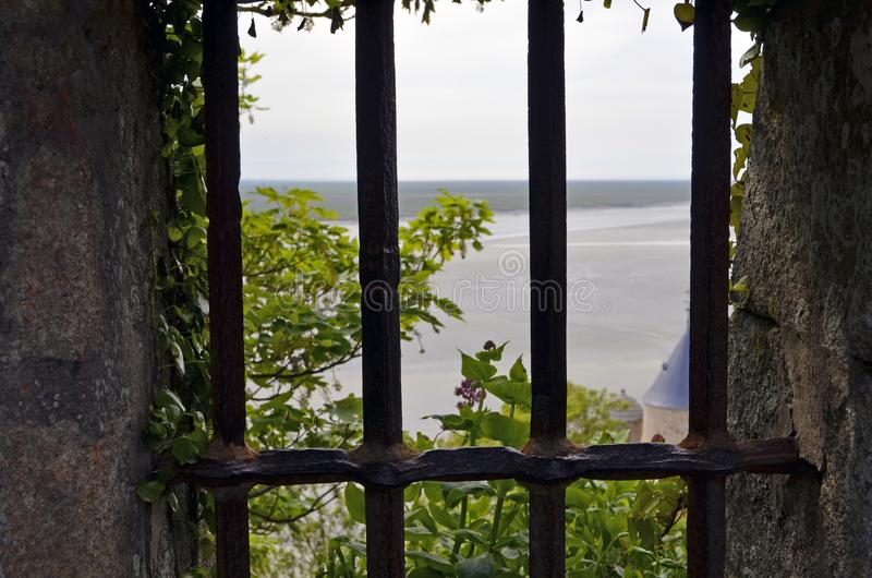 Ocean and meadows view from an old window with bars in Mont Saint Michele in France, Normandy. Ocean and meadows view from an old window with bars in Mont Saint royalty free stock image