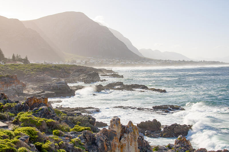 Ocean meets land at Hermanus, Western Cape. Tidal surge at Hermanus where the Atlantic Ocean meets the rocky landscape, with hazy mountains in the background royalty free stock photography