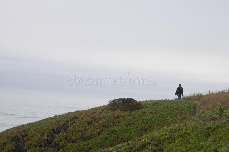 Ocean mist with a lone figure walking the path at Bodega Head. Bodega Point, California January 19, 2019 After days of heavy storms, finally a short break stock photos