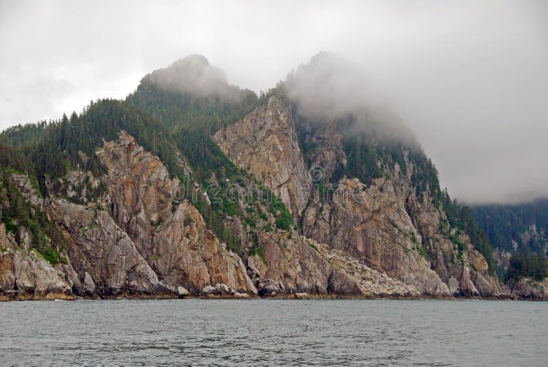 Ocean Monoliths in the Fog. Coastal Rocks in the fog in Kenai Fjords in Alaska royalty free stock image