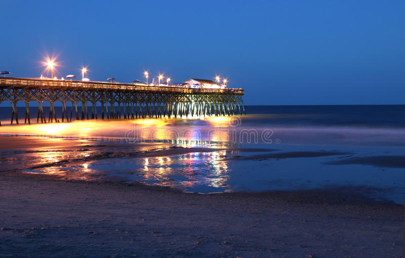 Ocean pier at night. Atlantic ocean pier with bright lightening during the beautiful summer night. Surfside Beach, Myrtle Beach area, South Carolina, USA royalty free stock image