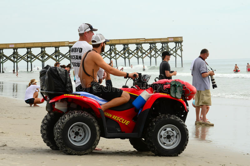 Ocean Rescue on ATV. Ocean rescue patrolling at Wrightsville Beach, NC on ATV with full gear, during the 2013 East Coast Wahine Surfing Contest royalty free stock image