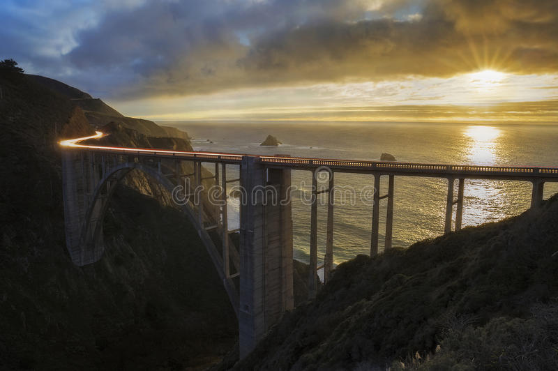 Ocean Road. Cars travel across the historic Bixby Bridge in Big Sur, California as the sun falls beyond the Pacific Ocean royalty free stock image
