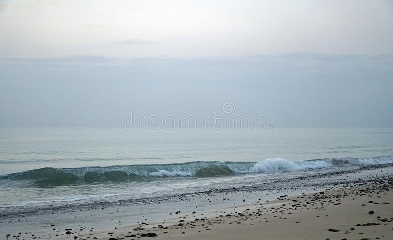 Ocean. Running surf waves on the beach. Early in the morning a few minutes before sunrise royalty free stock image