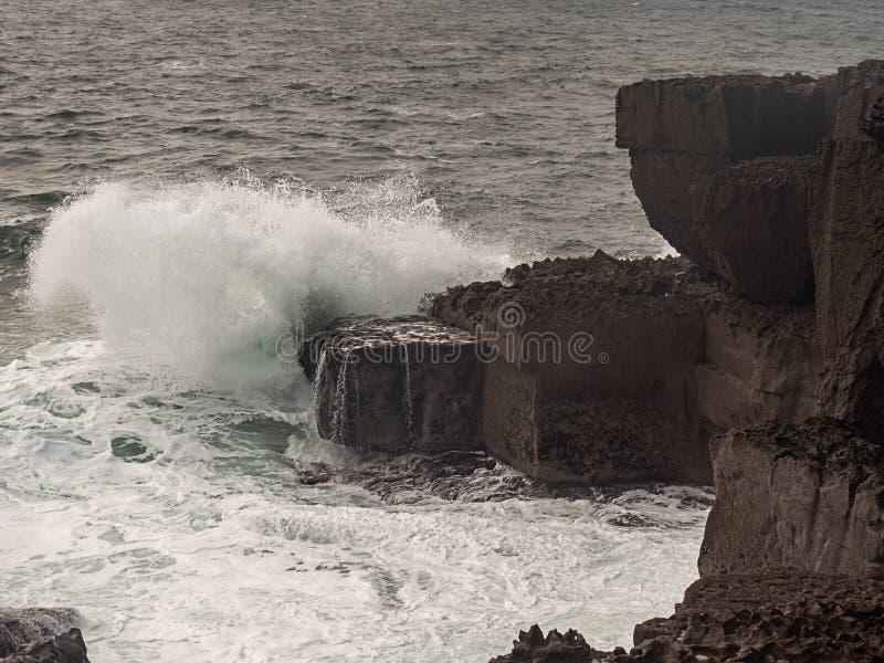 Ocean`s wave crashes on big stone creating splash of water, West coast of Ireland, Burren region royalty free stock photography