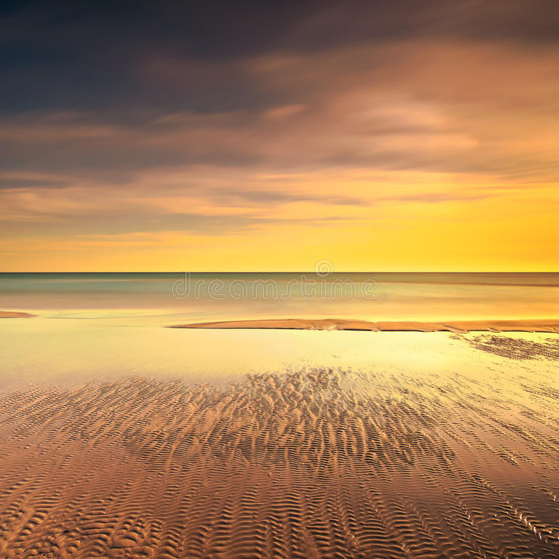 Ocean sandy beach line and warm sunset royalty free stock image