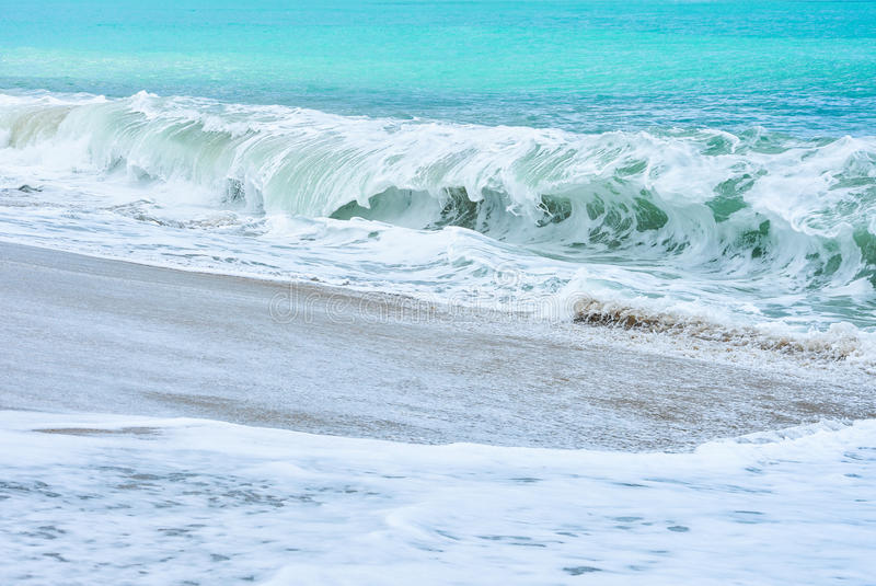 An ocean shorebreak in front view. Big beautiful green blue wave splashing with backwave and ready to break out. White foam. Sliding over sand. powerful ocean stock photo
