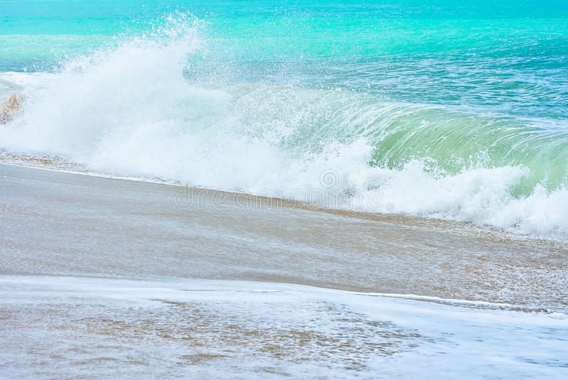 An ocean shorebreak in front view. Big beautiful green blue wave splashing with backwave and ready to break out. White foam. Sliding over sand. powerful ocean stock photography