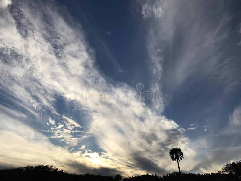 A beautiful scene of blue skies over the Atlantic Ocean in Florida. The ocean is a striking blue as sunset nears in Central Florida. The clouds are serene and royalty free stock photos