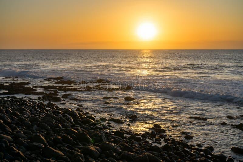 Ocean sun sets against lava shoreline in Canary Island, Spain.  stock photos