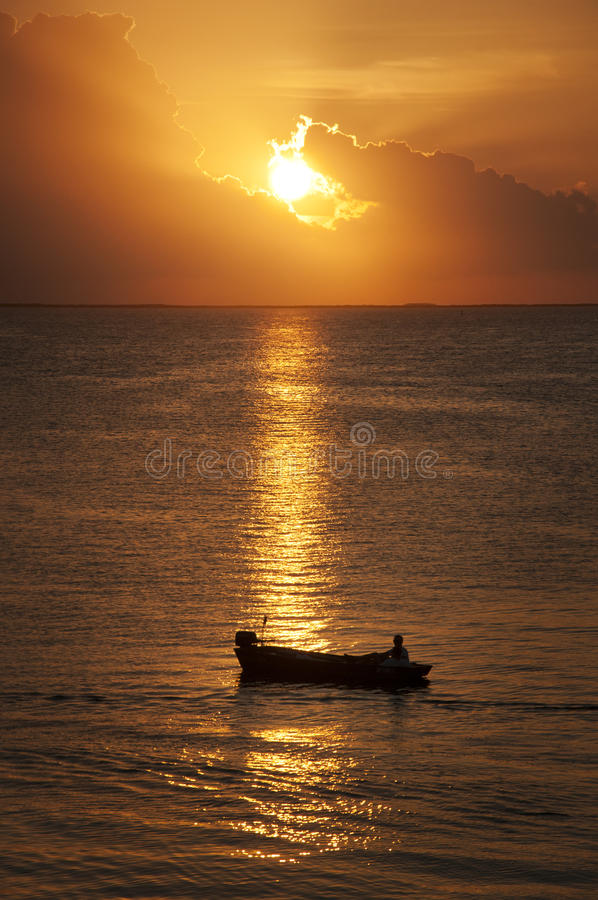 Ocean sunset. A bright golden sunset on a calm ocean with a small boat in the sun ray reflections. Destination scenic Key Largo, Florida