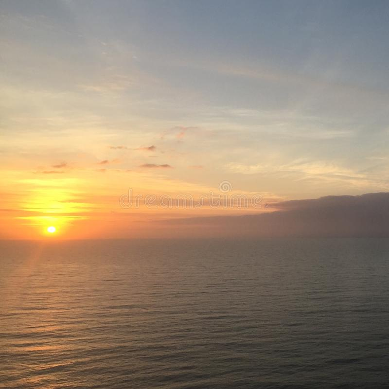 Ocean Sunset with a Horizon Line and Sun Reflection. Birds Eye View of the Horizon, Sky, Clouds, Water and Sun reflecting with Orange, Yellows gray and Blue stock image