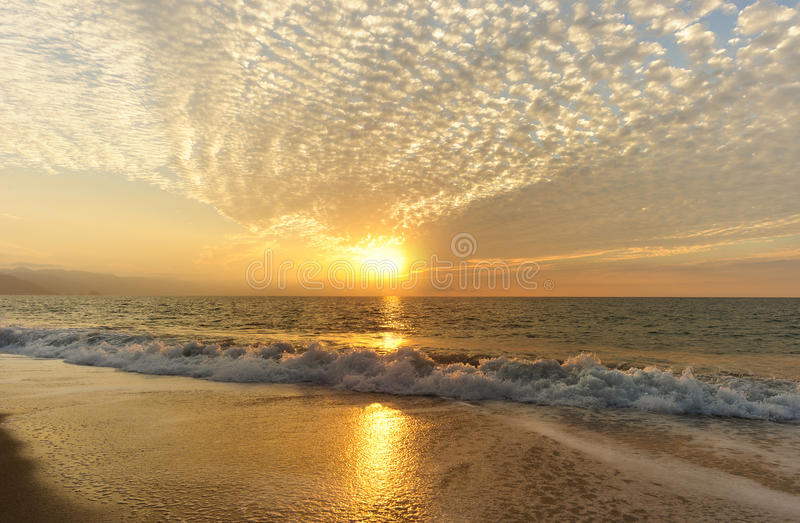 Ocean Sunset. Is a patterned cloudscape with a golden setting sun as gentle wave rolls to shore royalty free stock image