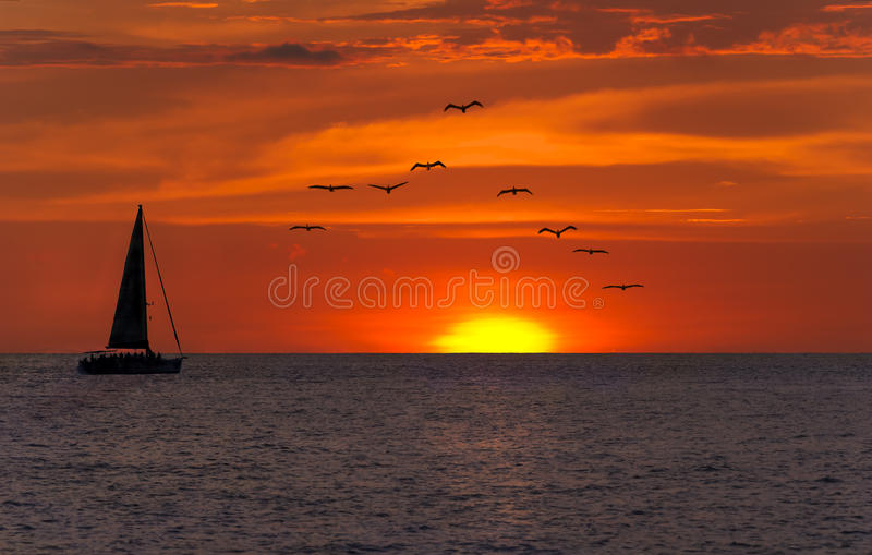 Ocean Sunset Sailing Fantasy. Is a bright yellow sun setting against a vivid red sky as a sailboat sets on its journey as a flock of seabirds fly overhead stock photography
