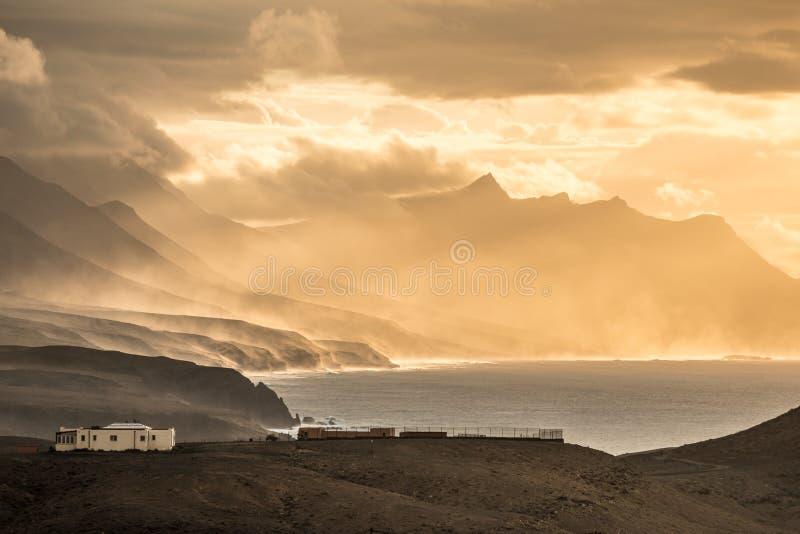 Ocean sunset scenery with mountainous coastline and epic light atmosphere stock photos