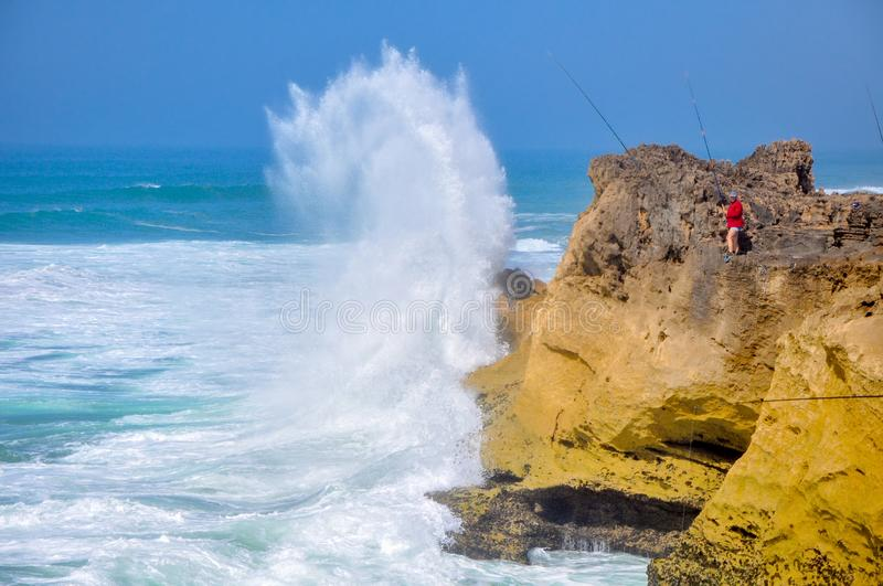 Huge waves are breaking about the rocky coast of the Atlantic Ocean, on the shore fishermen stock images