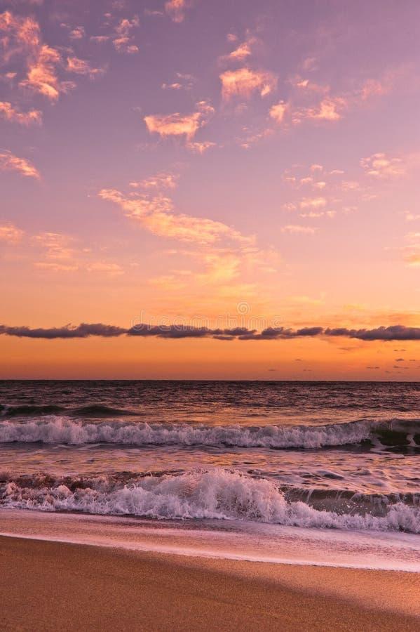 Ocean surf under golden clouds stock photos