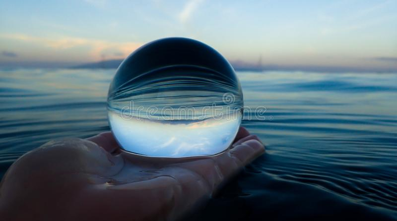 Ocean Surface Ripples Captured in Glass Ball. Ocean surface lines and ripples with island on horizon captured close up in glass ball royalty free stock images