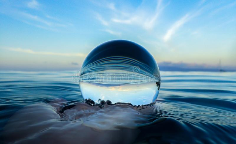 Ocean Surface Ripples and Clouds in Sky Captured in Glass Ball. Ocean surface with lines texture and ripples captured close up in glass ball royalty free stock photos