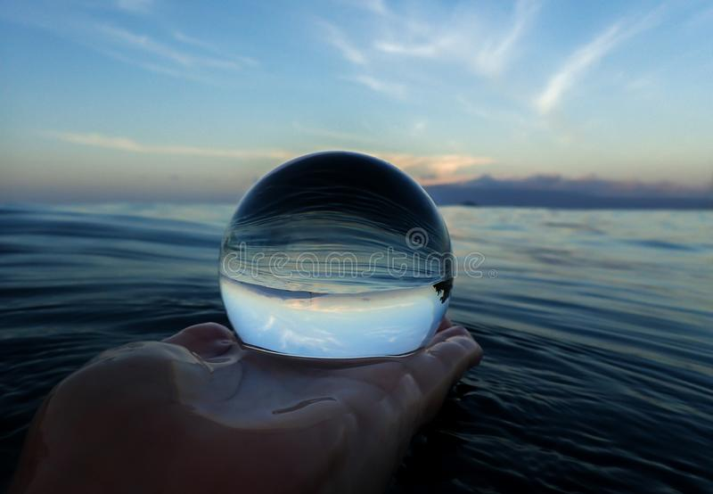 Ocean surface lines and textures with island on horizon captured in ball royalty free stock photo