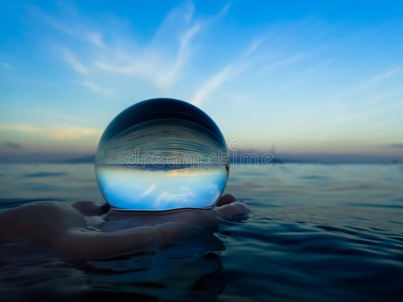 Ocean Surface Reflection in Glass Ball Held in Hand in Water. Ocean surface with sky and horizon emphasizing textures and lines captured in glass ball royalty free stock photo