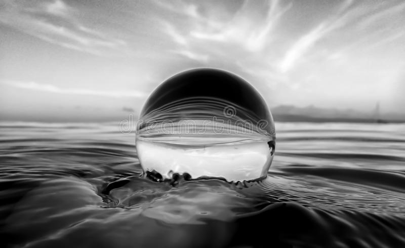 Ocean Surface Ripples and Clouds in Sky Captured in Glass Ball. Textures and lines in ocean surface and clouds in sky captured in glass ball royalty free stock photography