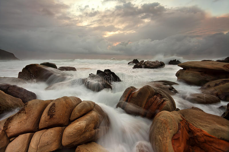 Ocean surges over weathered rocks. The ocean surges over well weathered rocks at Forresters Beach NSW Australia stock images