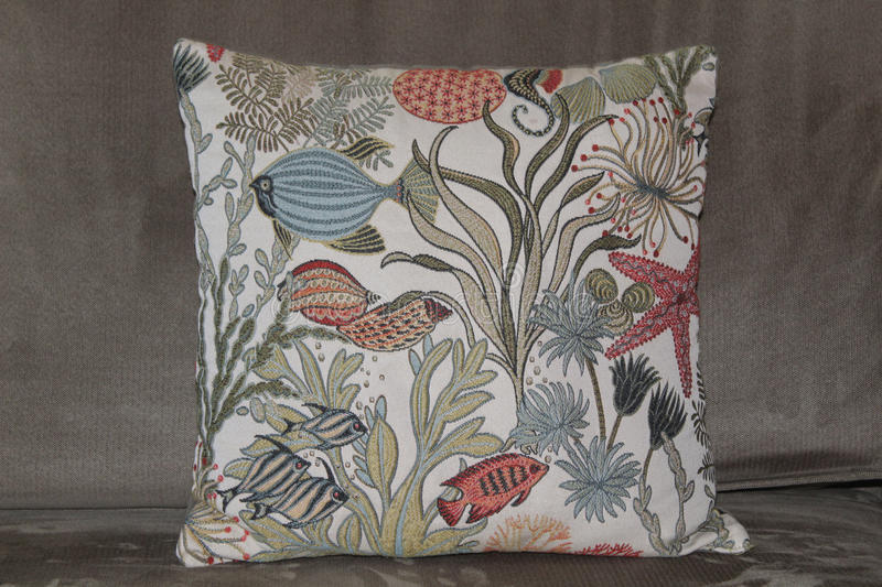 pillow with fish & ocean plants on a couch stock photo