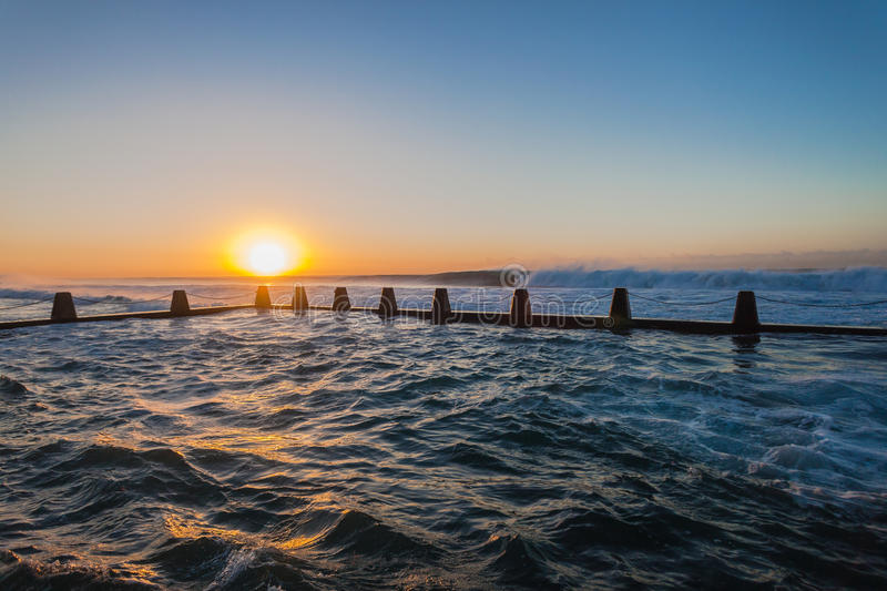 Ocean Tidal Pool Waves Sunrise. Ocean waves surging and crashing on high tides with swells breaking large powerful volumes of sea water into the concrete tidal royalty free stock images