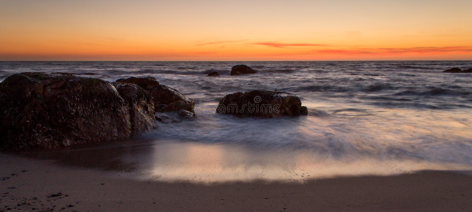 Incoming Tide at Sunset. The ocean tide changes during sunset with a few rocks in the sand royalty free stock photo