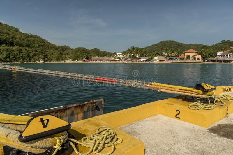 The beach and beachfront bars in Santa Cruz Huatulco from the cruise terminal dock. Huatulco is a resort region in the Mexican state of Oaxaca with white royalty free stock image