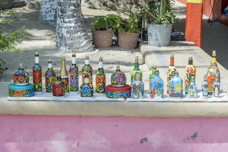 Upcycled bottles and tins display at a beachfront bar Santa Cruz Huatulco. Huatulco is a resort region in the Mexican state of Oaxaca with white Pacific coast stock photo