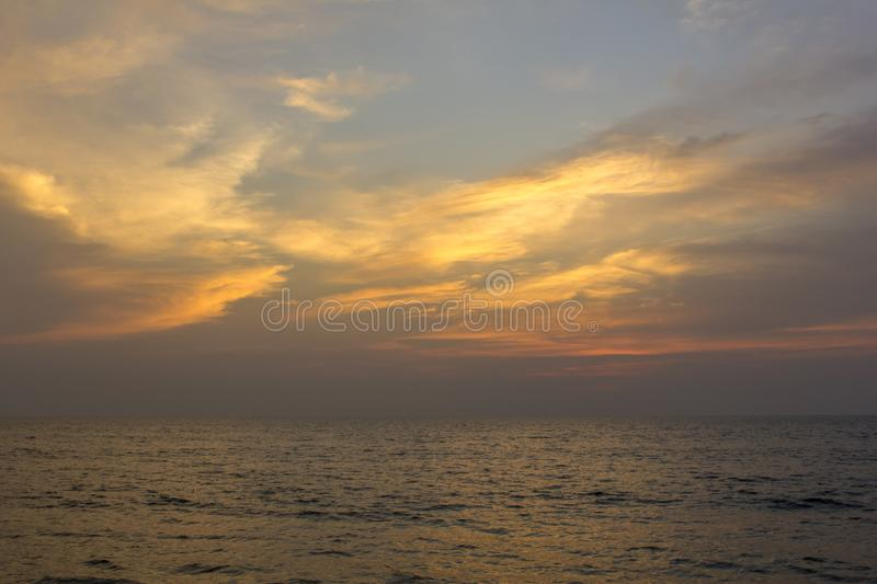 Ocean under purple sunset sky with bright orange clouds. A ocean under purple sunset sky with bright orange clouds stock photo