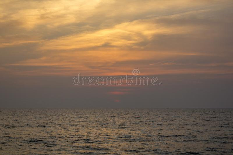 Ocean under a purple sunset sky with bright yellow clouds. A ocean under a purple sunset sky with bright yellow clouds stock photography