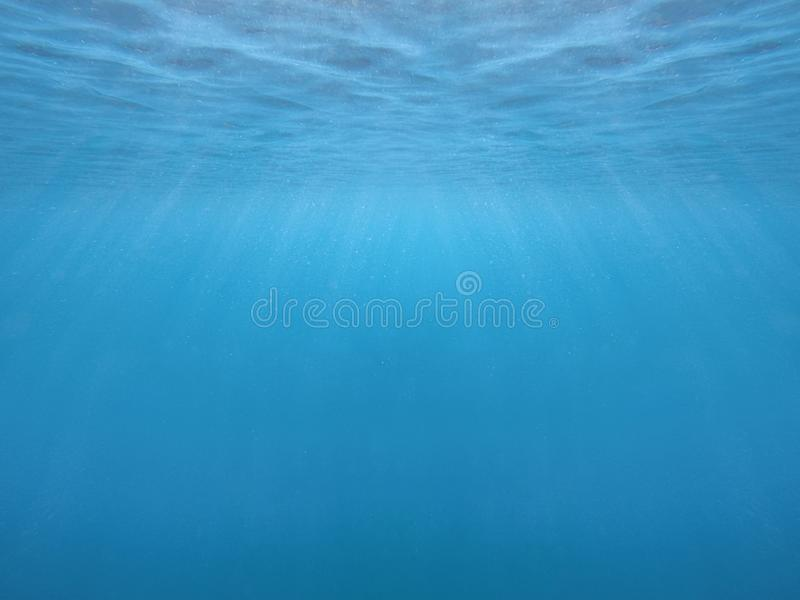 Blue water surface and ripples with rays of light under water.  stock photos