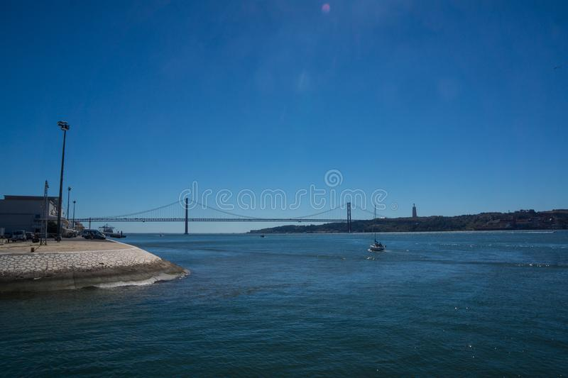 Ocean with view on bridge of 25th april stock image