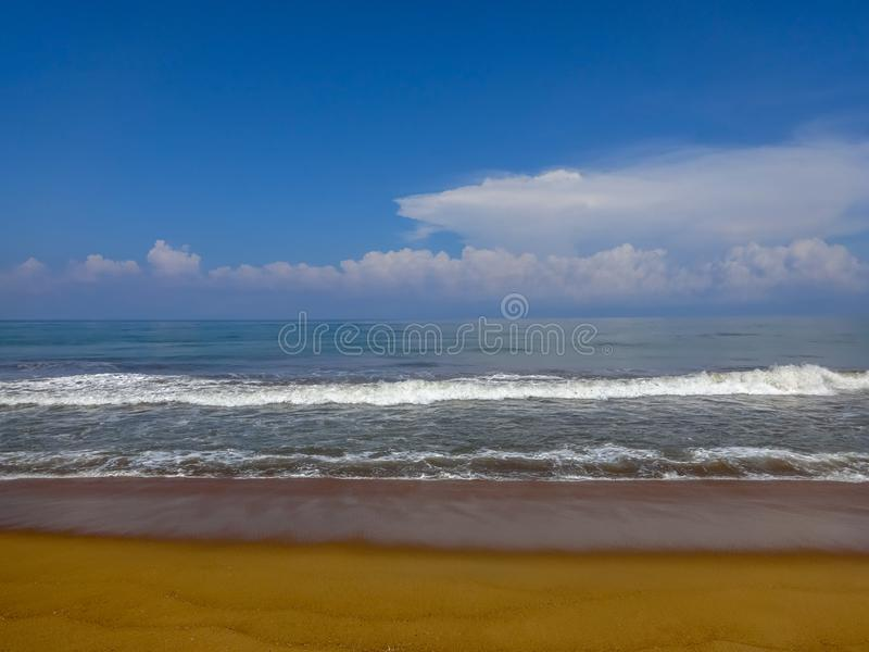 Scenic view of the Indian ocean against blue sky in Kalutara, Sri Lanka. Waves at the wild beach in Kalutara, Sri Lanka royalty free stock photo